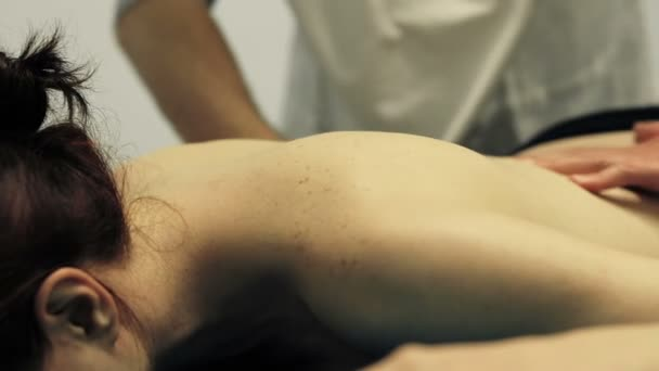 therapeutical massage: physiotherapist is massaging cute young girl