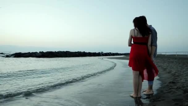 Young couple near the sea at sunrise