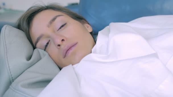 mladá žena, ležící, spící na gauči doma