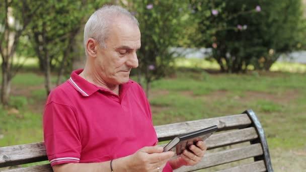 Rentner ruht sich aus und bedient sein Tablet am Tisch im Park
