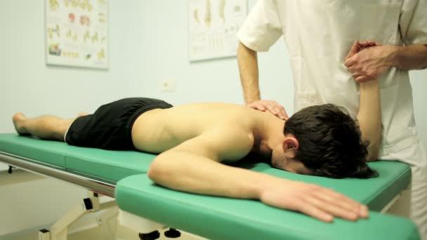 fyzioterapeut provádí pohyby v kloubu ramene mladý pacient
