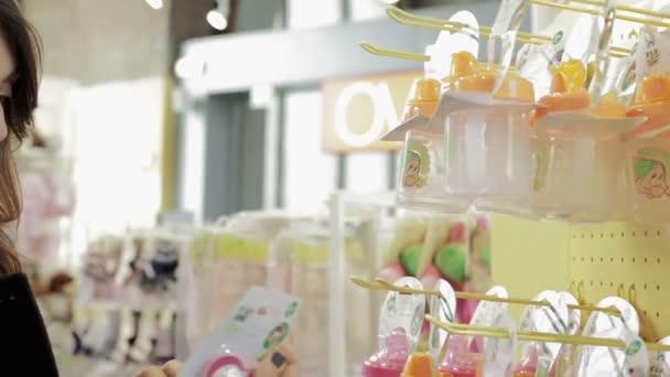 Atraktivní mladá matka nakupování pro dětské biberon v kamenném obchodě