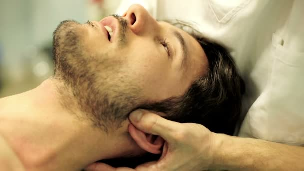 physiotherapist is doing massage to the face: the neck, muscles, nerves, tendons