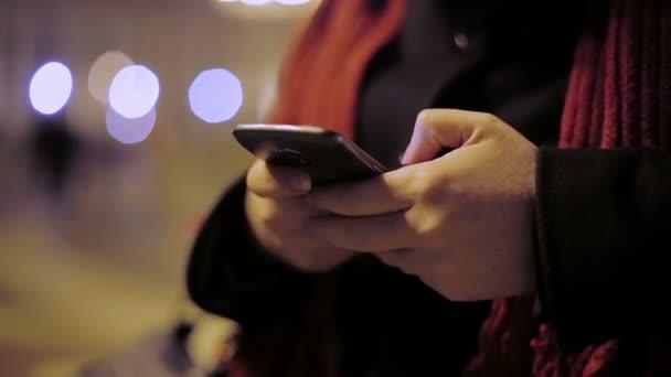 nő használ smartphone a városban éjszaka