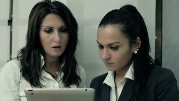 Businesswomen using a digital tablet while having a meeting