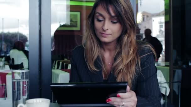 Young businesswoman using tablet computer in cafe