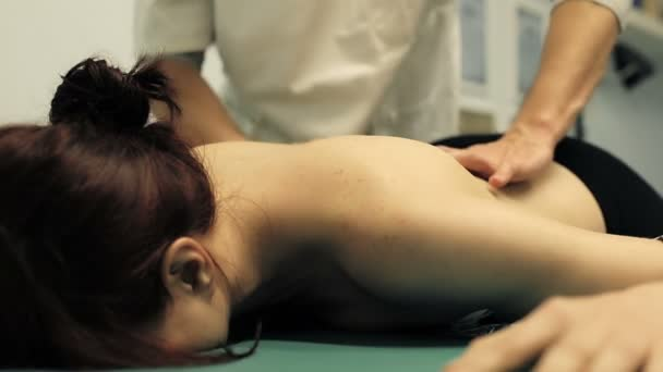 therapist is doing a massage to a young cute girl: masseur; massaging
