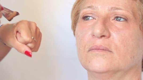 Kosmetikerin schminkt