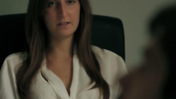 Beteg nő ül a kanapén, és beszél a pszichológus nő