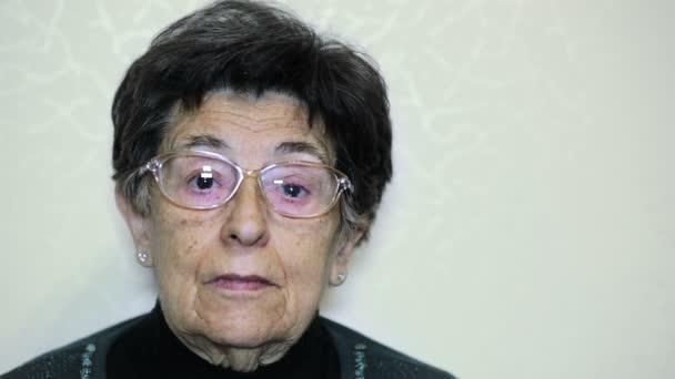 Porträt einer nachdenklichen, traurigen alten Frau, die in die Kamera blickt