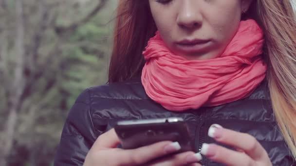 Žena pomocí mobilního telefonu v parku