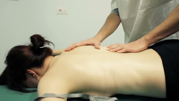 young girl is having massage: masseur, massaging, physiotherapist.