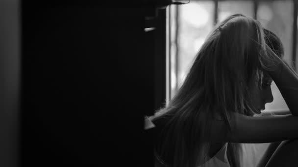 mladá dívka sedí u okna