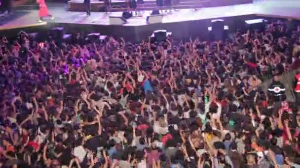 overview of huge crowd of people dancing and clapping his hands during a concert