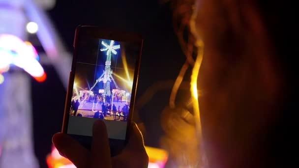 Ruka s smartphone s video v zábavním parku