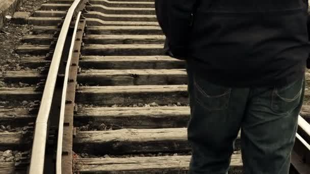 Muž odchází uprostřed tratí