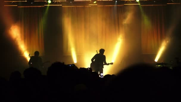 silhouette of a rock concert: musicians, guitarist, stage, audience