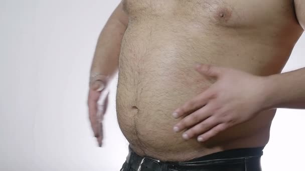 fat man hitting his belly with hands: overweight, obesity, diet, healthcare