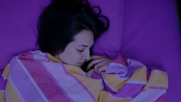 Unavená žena spí v posteli