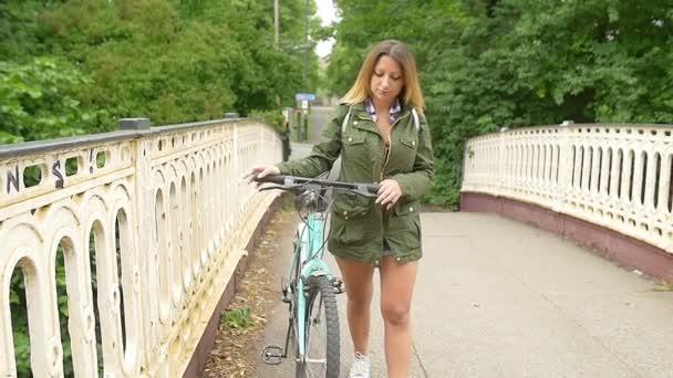 Mladá žena chůze nohy s její kolo na mostě