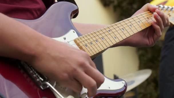 kytarista hrající elektrickou kytaru na koncertě