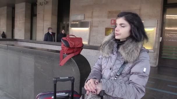 Žena na platformě s kufry čeká na odlet s vlakem