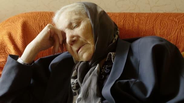 depressziós idős asszony ül a kanapén