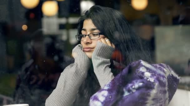 Pensive, thoughtful beautiful woman drinking coffee in cafe