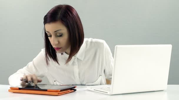 young woman at work on a white lapotop and tablet computer