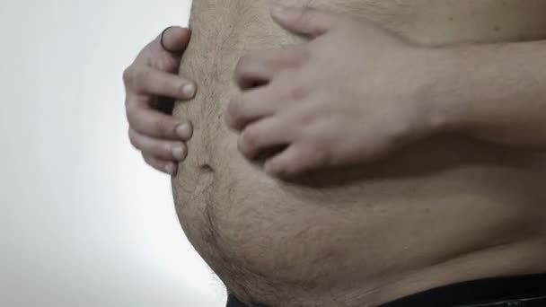 overweight problems: man hits his belly with his hands