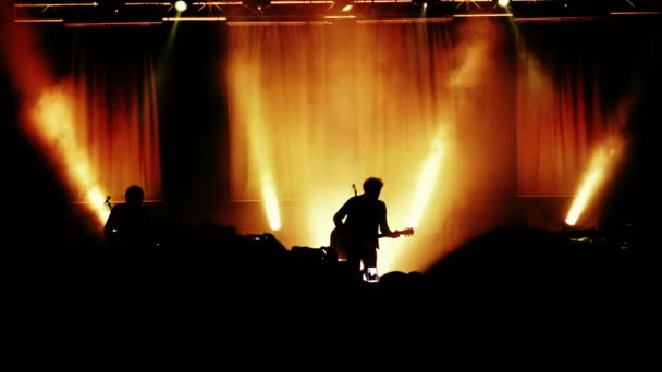 rock concert: silhouette of guitarist playing on the stage