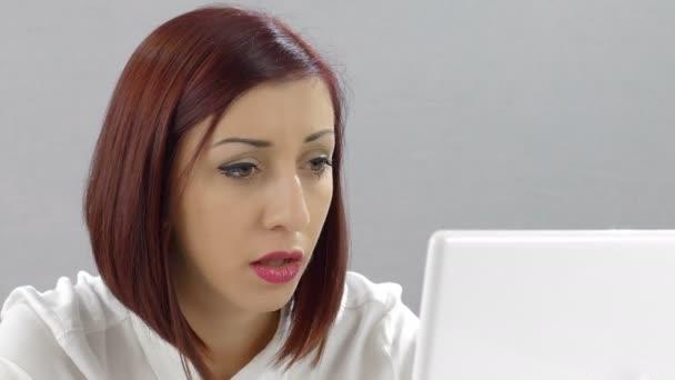 Besorgte und müde junge Frau arbeitet mit Laptop-Computer: Büroangestellte
