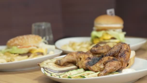 dishes of fast food: hamburgers, chicken, French fries, salad