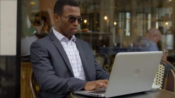schwarze elegante Geschäftsmann arbeitet mit seinem Laptop sitzt in einem Café in der Stadt