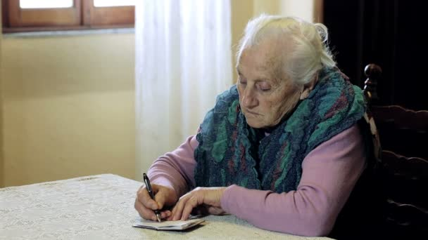 old woman is writing on little notepad: pen, paper, older, ancient, notes, takes