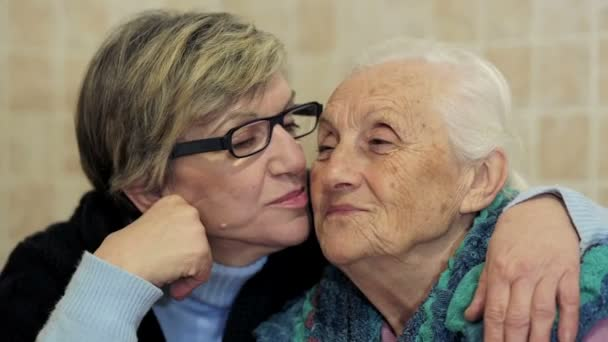 daughter kissing her old mother