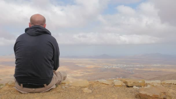 bald man sitting on top of the mountain