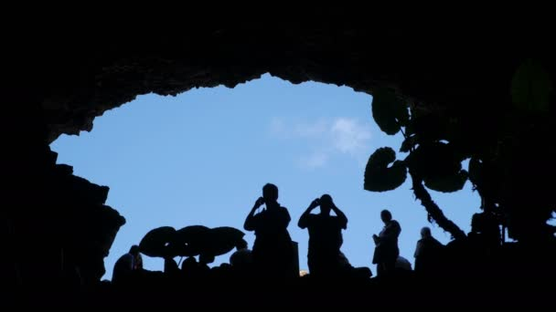 Lanzarote-  crowds of tourists in the shadows under a cave arch