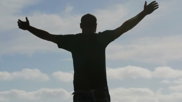 man backlit raises his arms to the sky