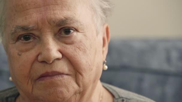 Ältere Frau blickt stolz und zufrieden in die Kamera