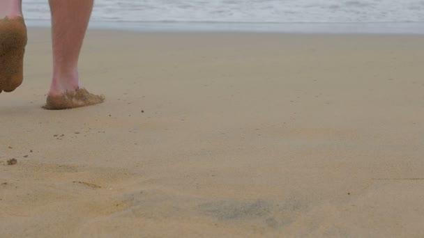 a gyalogos séta a homokot az ember és a tenger felé megy