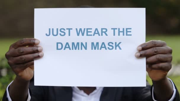 black mans hands hold the placard: just wear the damn mask