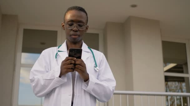 covid19 - black doctor checks the phone before returning to the ward