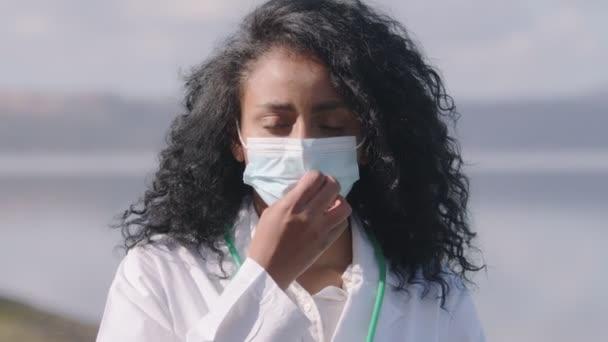 Hoffnung, Positivität - junge hispanische Ärztin zieht ihre Maske herunter und lächelt
