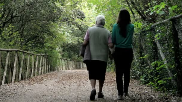 old woman and her young granddaughter taking a walk in the park