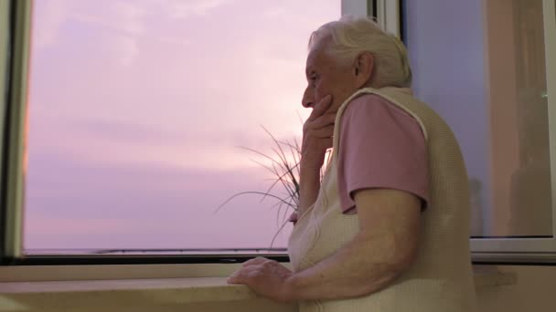 Sad and lonely old woman looking out window - depressed - sunset