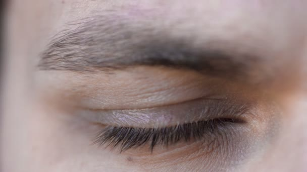 krásný mladý muž otevřít své modré oči a dívá do záběru kamery 4k