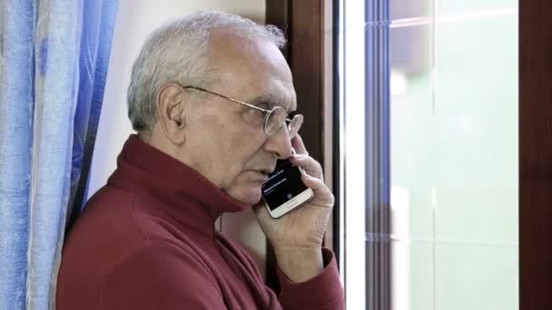 idős ember, miután egy telefon hív, az ablak mellett: mobiltelefon, mobiltelefon
