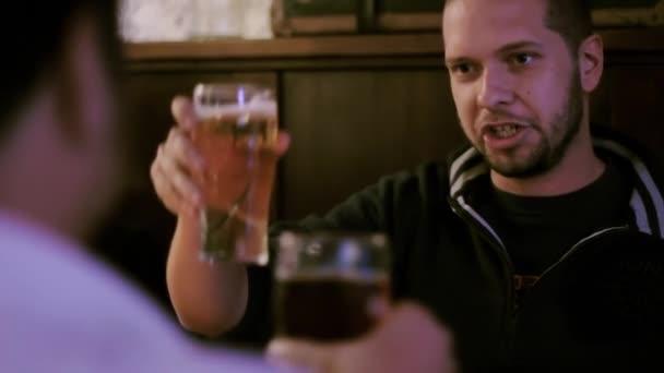 Due uomini che tostano birra in un pub