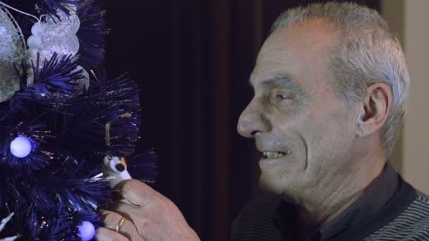 starší muž, zdobení vánočního stromu